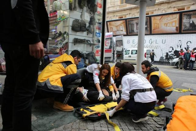 A man is helped by emergency services members following a suicide bombing in a major shopping and tourist district in central Istanbul March 19, 2016. REUTERS/Kemal Aslan