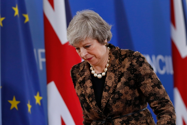 British Prime Minister Theresa May walks by the Union Flag and EU flag as she departs a media conference at an EU summit in Brussels, Friday, Dec. 14, 2018. European Union leaders expressed deep doubts Friday that British Prime Minister Theresa May can live up to her side of their Brexit agreement and they vowed to step up preparations for a potentially-catastrophic no-deal scenario. Associated Press/Alastair Grant