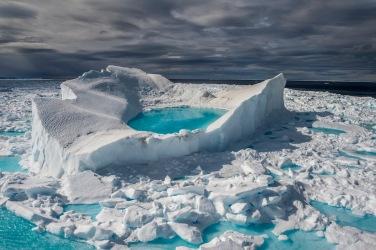 Iceberg in fusione ai margini dell'Isola di Baffin (Artico Canadese). Le datazioni al radiocarbonio di resti vegetali prelevati presso le fronti glaciali indicano che i ghiacciai della zona si trovano nelle posizioni più arretrate in ben 40.000 anni. © Brian J. Skerry